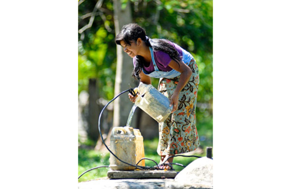 Madalena from Salele in the Suai district draws water from a well. Photo by UNMIT/Bernardino Soares