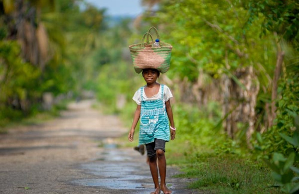 A girl from Suai carries goods on her head as she returns home from the market. Photo by UNMIT/Berna