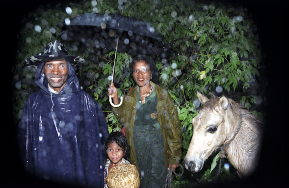A family from Ainaro walk home under the rain. Photo by UNMIT/Martine Perret