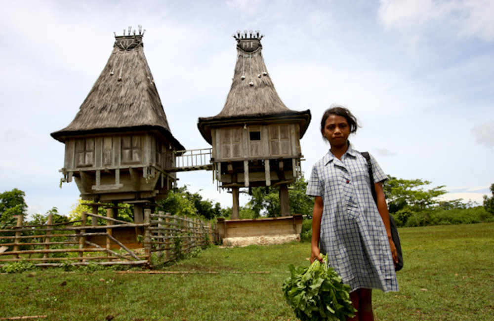 A schoolgirl from Mehara stands in front of two traditional houses. Photo by UNMIT/Martine Perret