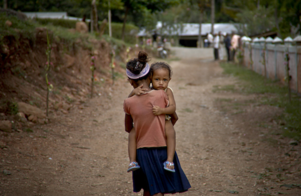 A young girl carries her brother to the water well in Maubara. Photo by UNMIT/Bernardino Soares