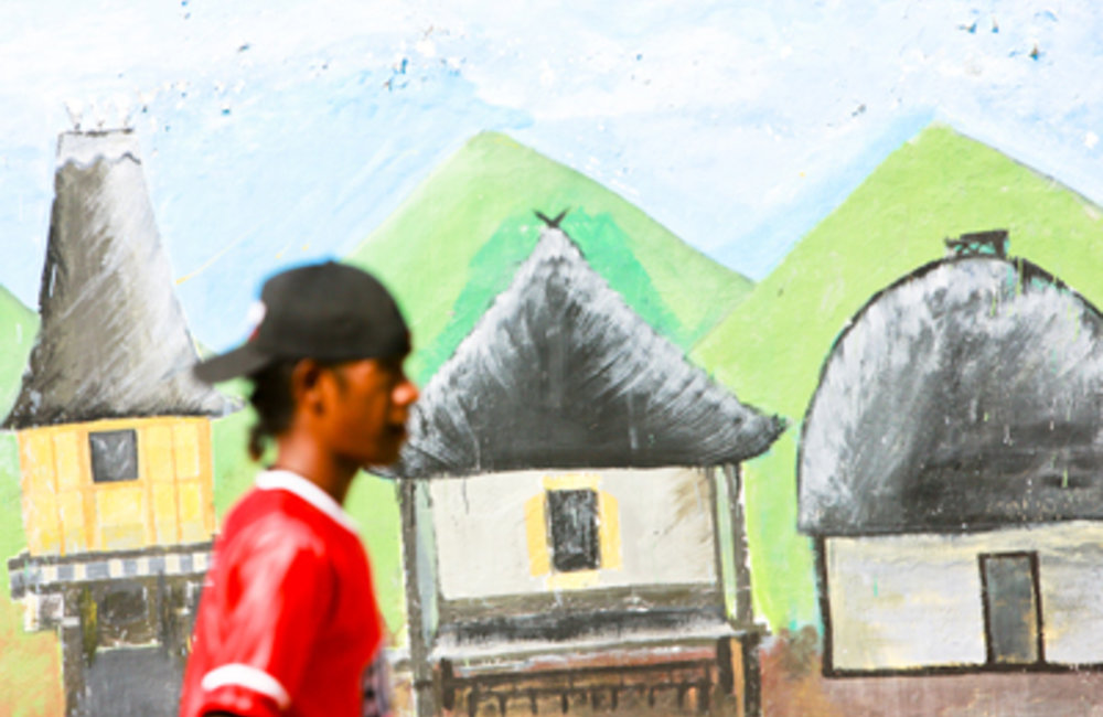 A young man walks past murals at the Dili stadium after a football match. Youth unemployment is one