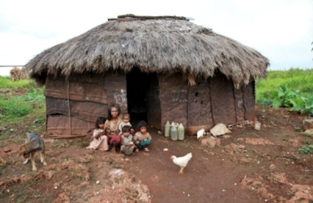 A mother with her children in Baucau rest at their house, which is made of corrugated iron and has a
