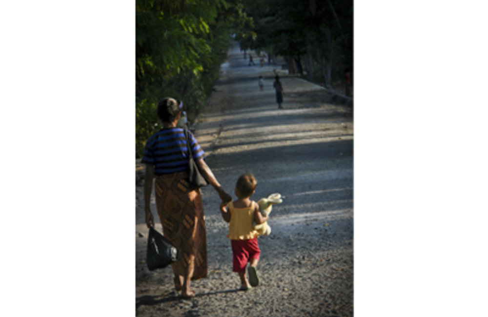 A mother and child walk down the main street of Vila in Atauro. Photo by UNMIT/Martine Perret