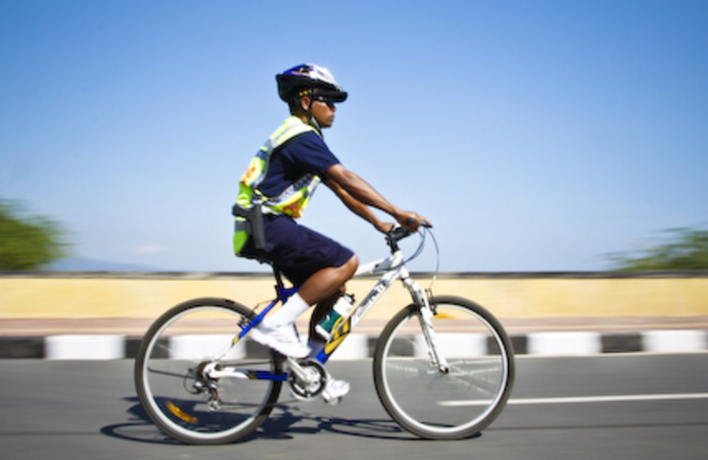 Timorese police officer patrols on bicycle around Cristo Rei beach in Dili. Photo by Bernardino Soar