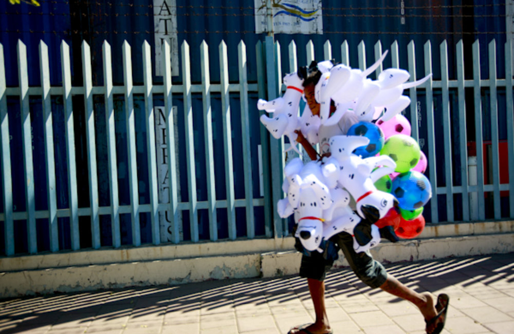 Young man carries plastic toys for sale. Photo by UNMIT/Martine Perret