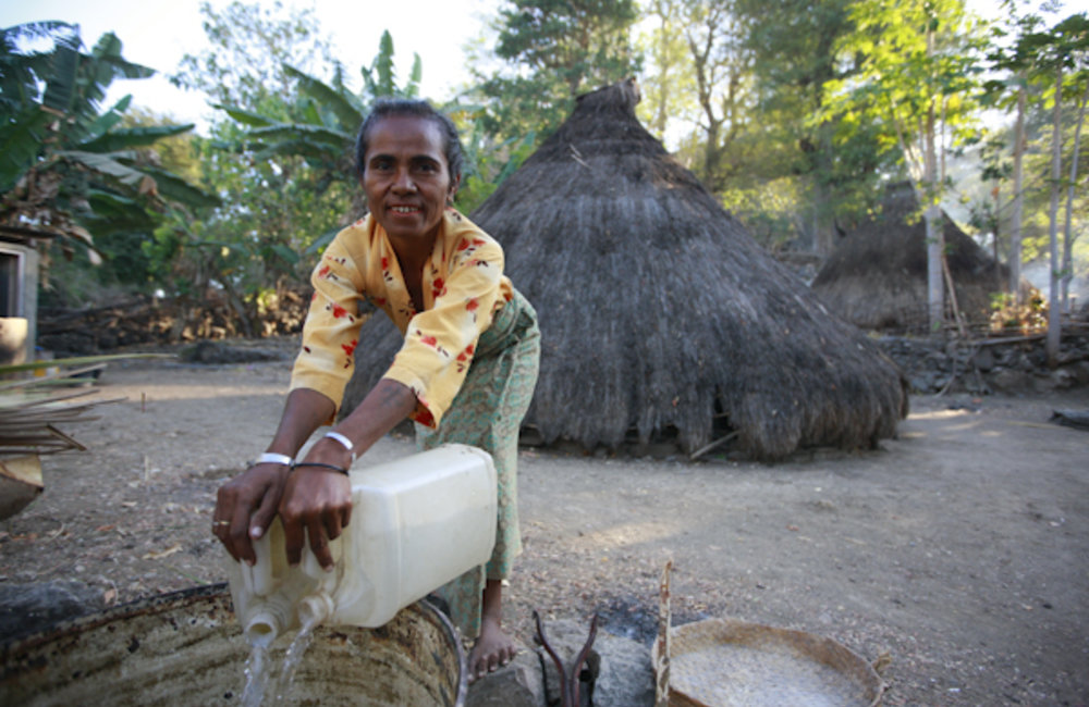 A woman from Pune, in Oecusse, stores water in a barrel. Photo by UNMIT/Martine Perret