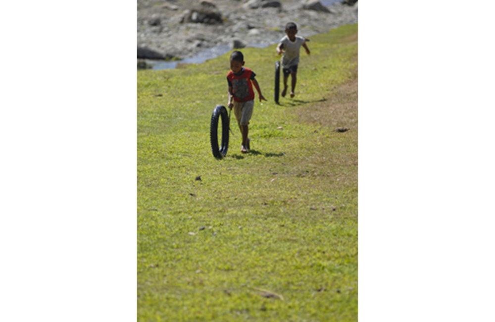 Children from Rai-laku push scrap tires. This simple game is very popular among Timorese children. U