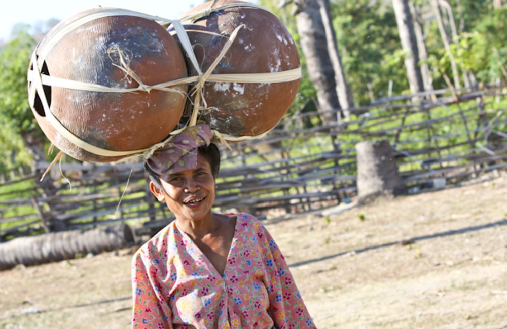 A woman carries her pots to Tono Market in Oecusse. Photo by UNMIT/Martine Perret