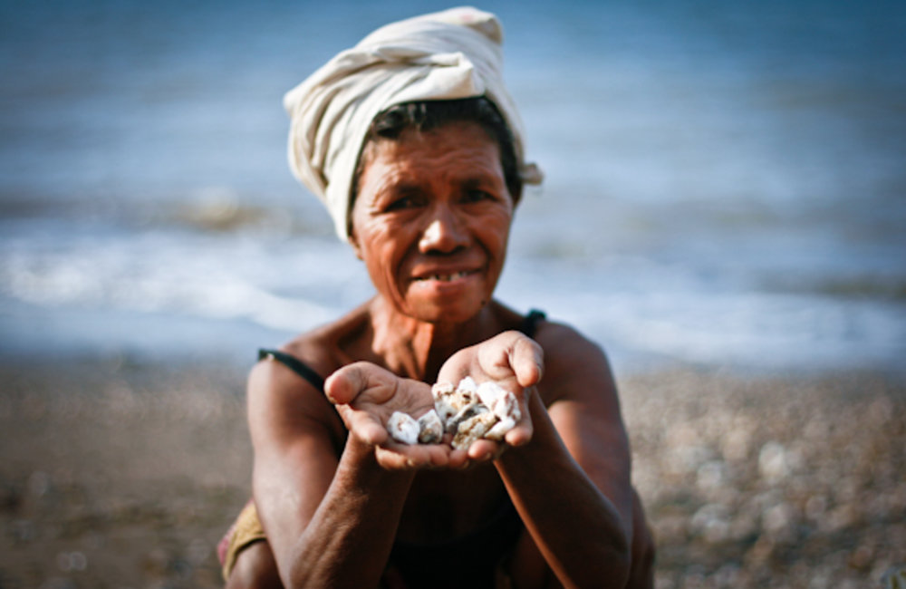 Teresa Perreira collects pebbles on the beach in Bidau, Dili. She sells the pebbles to people who us