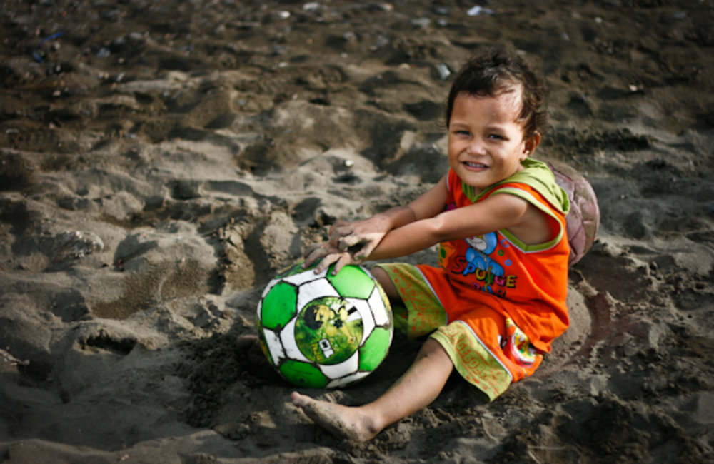 A child playing ball on the sand of Pantai Kelapa beach, Dili. Photo by UNMIT/Bernardino Soares