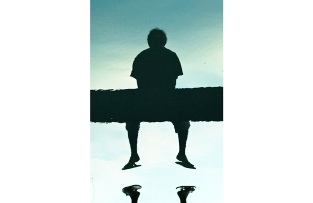 A boy sits on a bridge in Licidere, Dili, casting a shadow in the water below. Photo by UNMIT/Bernar