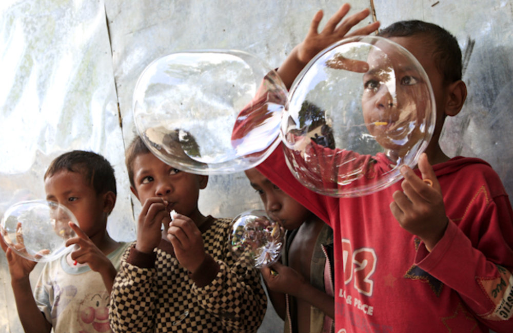 Best of UNMIT Photo of the Day: Children making water bubbles. Photo by UNMIT/Martine Perret
