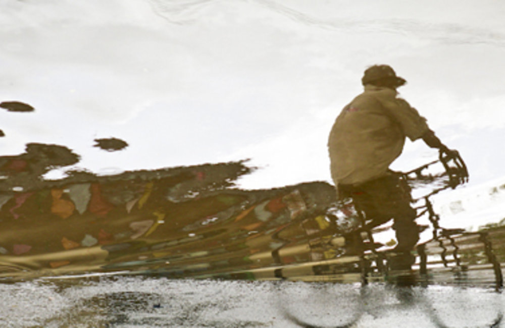 A man rides his bicycle under heavy rains in Dili. Photo by UNMIT/Martine Perret