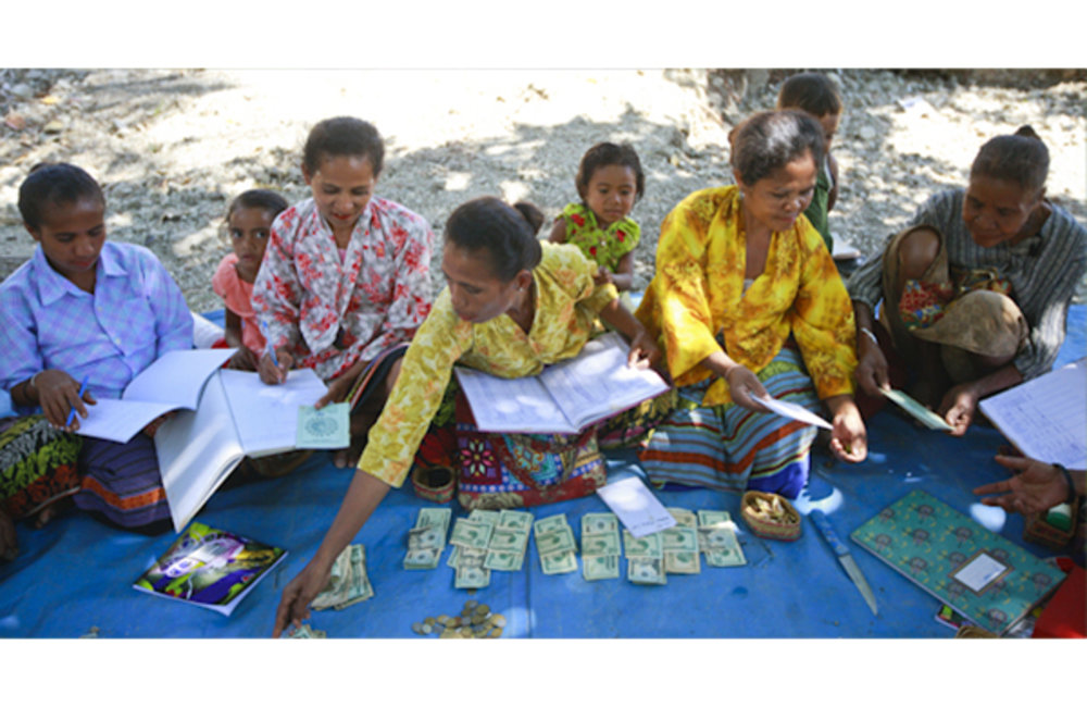 Women from a self-help group in Malelat, Oecusse contribute money to collective savings, which can t