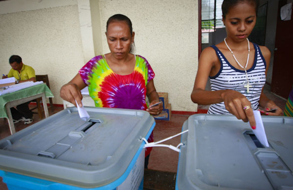Two women cast their votes in a polling station in Dili in the first round of the Presidential elect