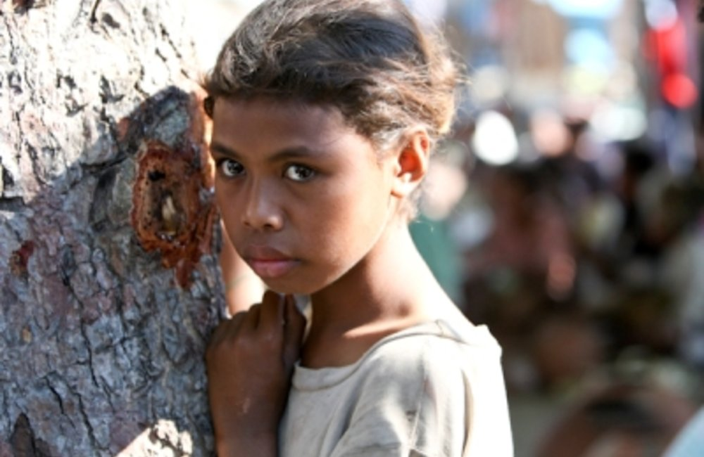 A young girl stands by a tree in Oecusse market. Photo by UNMIT/Martine Perret