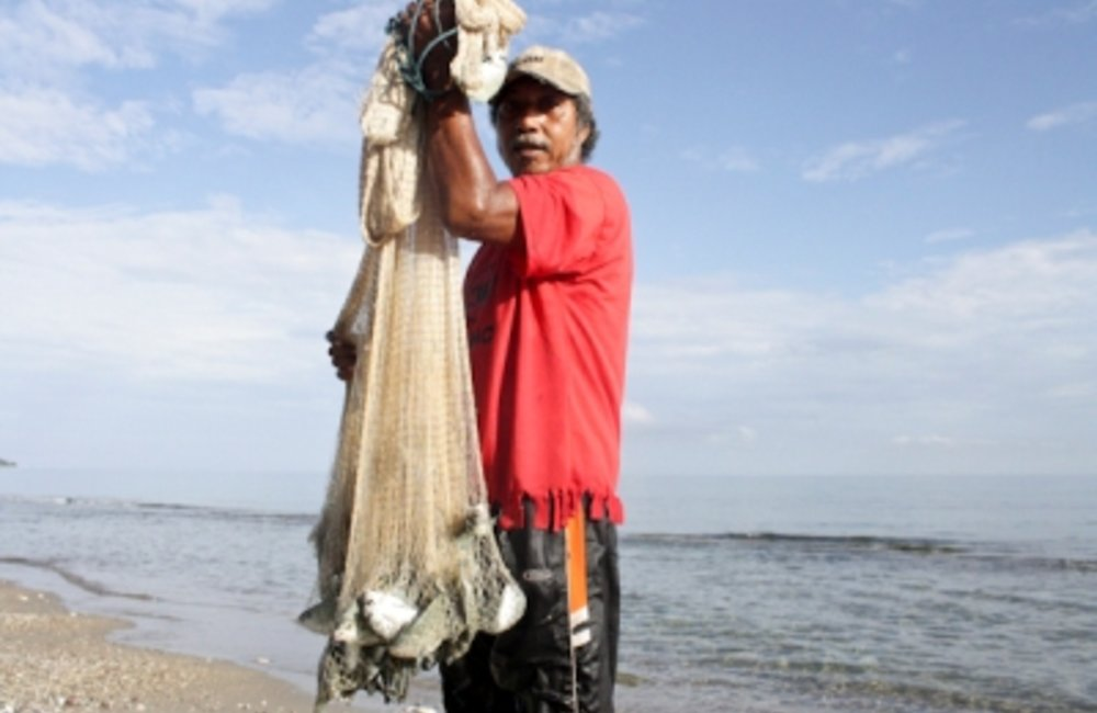 A fisherman shows his catch in Dili. Photo by UNMIT/Cesaltino Ximenes
