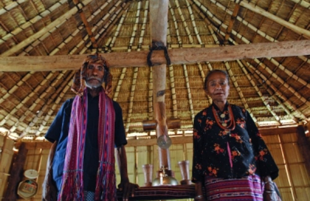 "Two elders from Maubara stand inside a sacred house "" Uma Lulik"" . Photo by UNMIT/Bernardino Soares"