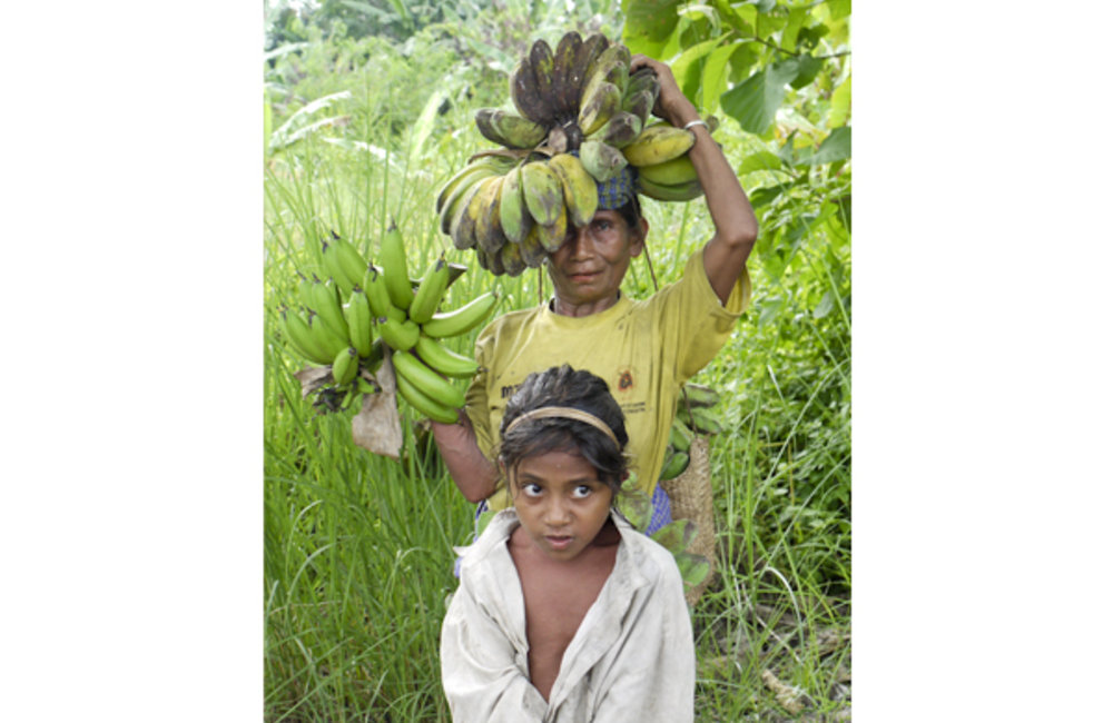 A mother and child carry bananas home. Photo by UNMIT/Cesaltino Ximenes