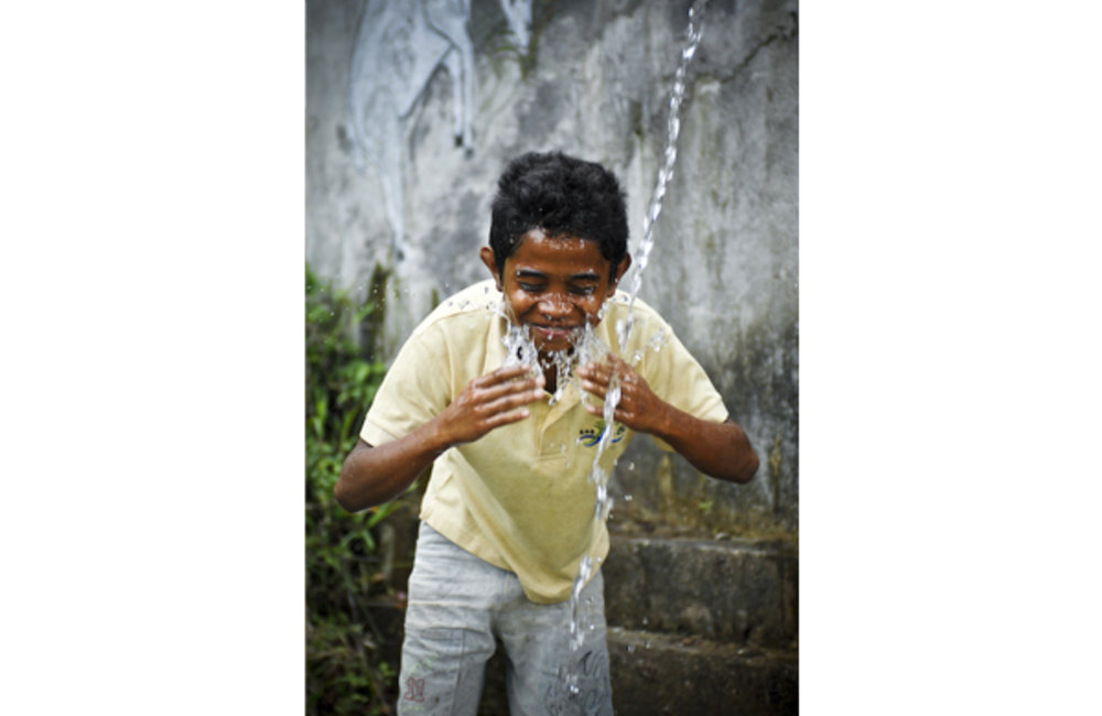 Juvito Do Rego, a young boy, washes his face from a water fountain in Dare, near Dili. Photo by UNMI