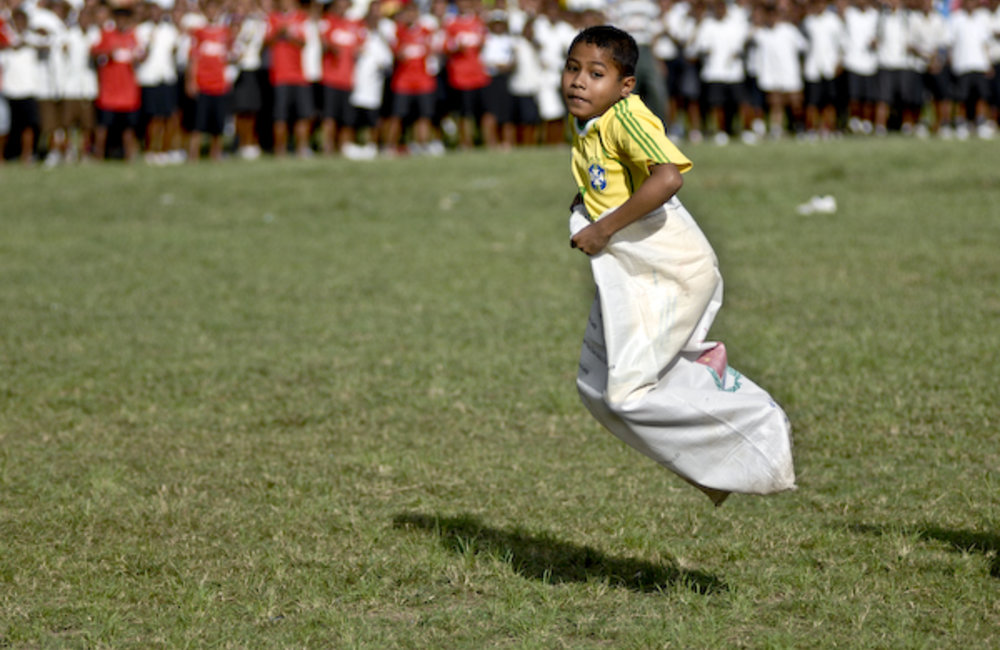A child participates in a sack race. Photo by Bernardino Soares/UNMIT