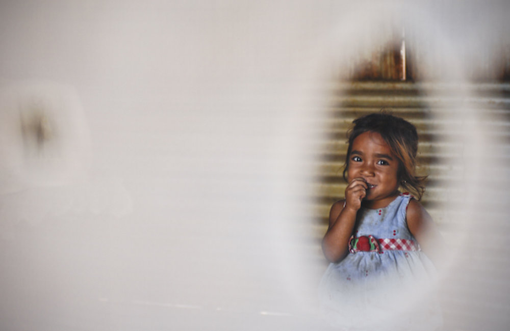A child looks through a window's curtain at Ritabou, Maliana district. Photo by Bernardino Soares/UN
