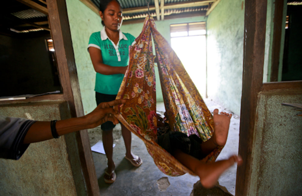 A woman weighs a baby using a sarong on a hook attached to scales, during a mobile clinic visit to E