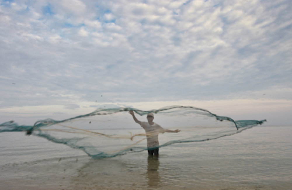A fisherman from Baucau throws his net to catch fish. Photo UNMIT/Martine Perret
