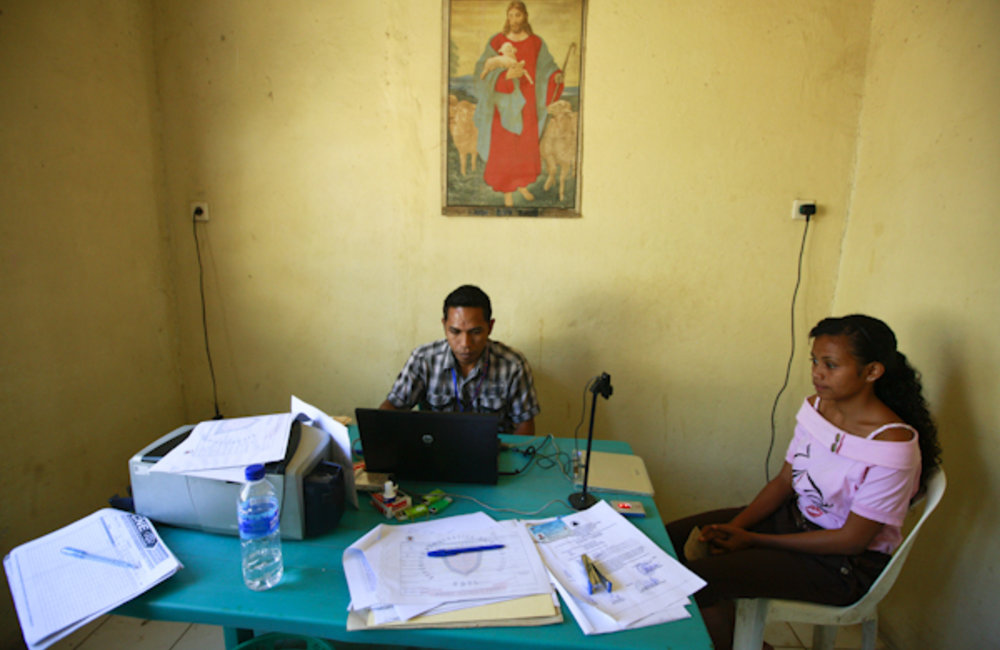 A staff member from the electoral management body, STAE, registers a new voter at the administration