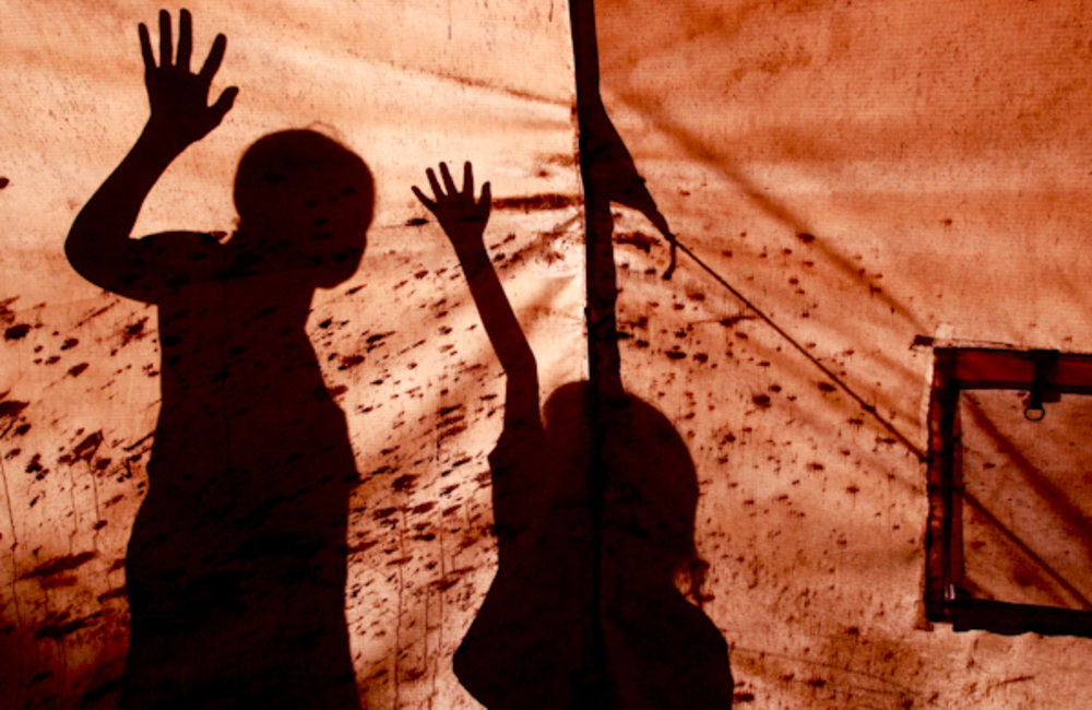 Children play behind a tent in Dili. Photo UNMIT/Martine Perret