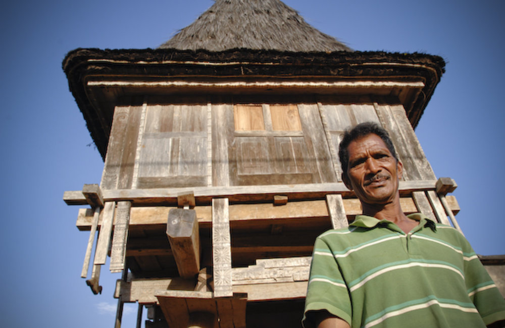 "Jacinto Almeida, stands in front of the community of Fuiloro's traditional house called ""Lere Sera M"