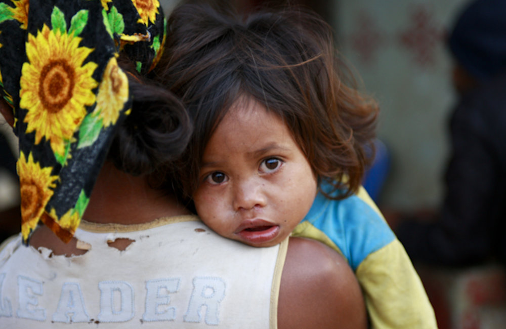 A mother from Lesuata carries her child during a community meeting. Photo by UNMIT/Martine Perret