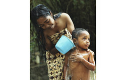 A woman from Betano washes her child by the village well. Photo by UNMIT/Martine Perret