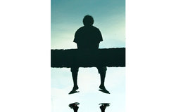 Best of UNMIT Photo of the Day 2011: A boy sits on a bridge in Licidere, Dili, casting a shadow in t