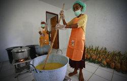 A woman working at the Centro de Desenvolvimento Comunitario (CDC) making marmalade from pineapple.
