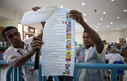 Staff from Timor-Leste's National Electoral Commission show a protested ballot to representatives of